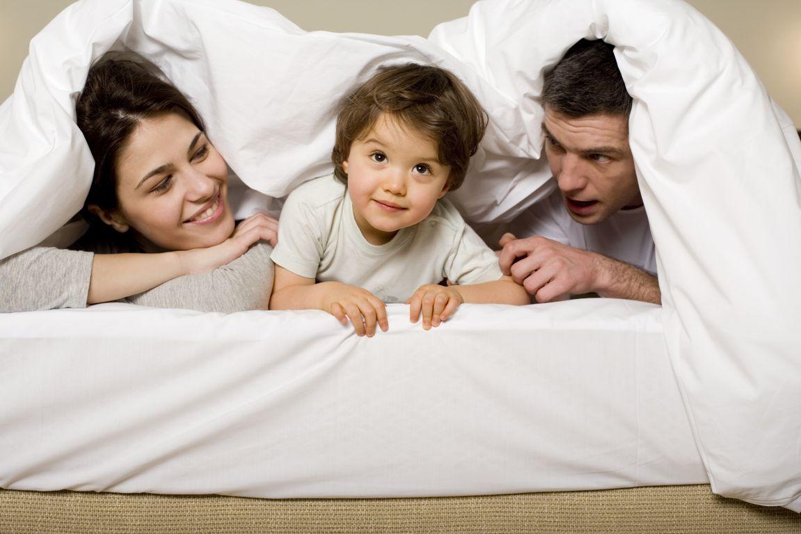 Family lying under bedspread